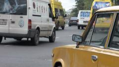 Traffic drives through Tbilisi, behind old Lada taxi Stock Footage