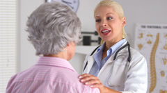 Doctor with hand on elderly patient's shoulder - stock footage