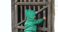 Upset little child try to open wood gate of a house Stock Footage