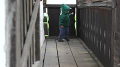 Cute little boy walk on wood veranda of old house Stock Footage