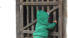 Little baby child pull at house wood door want to open and get in Stock Footage