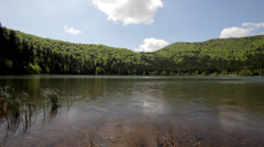 Velo Blue sky, white clouds moving fast and spring green forest reflect on lake  Stock Footage