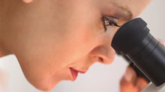 Close up side view of medical researcher looking into microscope - stock footage