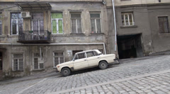 Classic Lada, Tbilisi streets, former Soviet Union, steep road, old houses - stock footage