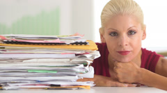 Business woman next to large stack of paperwork - stock footage