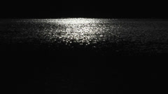 Moon light on the dark sea in night, white and black scenery - stock footage