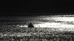 Lonely boat with paddles floating on the dark lake in the night Stock Footage