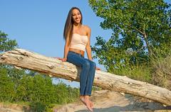 Beautiful young woman on log Stock Photos