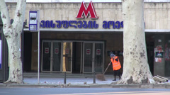 Sweeping the streets of Tbilisi, in front of metro entrance, early morning Stock Footage