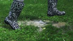 Woman in rain boots jumping into puddle, slow motion shot at 240fps Stock Footage