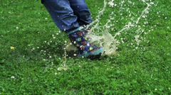 Child jumping into puddle, slow motion shot at 240fps Stock Footage