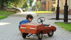 The three-year old boy examines a toy car Stock Footage