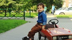 Cute three year old boy posing sitting on a toy car - stock footage