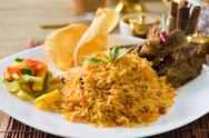 Stock Photo of biryani mutton rice papadam with traditional background