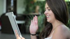 Smiling young woman sitting in a garden and chatting on tablet computer HD Stock Footage