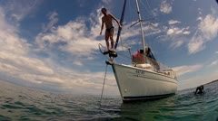 Man jumping into sea from boat in mediterranean Stock Footage