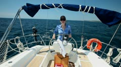 Woman at wheel steering sailboat on Adriatic sea in Croatia - stock footage