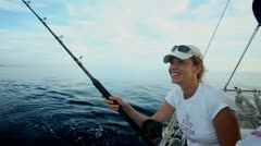 Woman fishing with rod on sailboat at sea Stock Footage