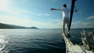 Stock Video Footage of Man standing on the bow of sailing boat on Mediterranean sea.