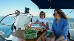 Friends enjoying food on board sailboat at sea - stock footage