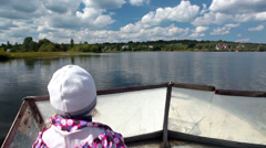 Driving motorboat with child standing at steering wheel Stock Footage