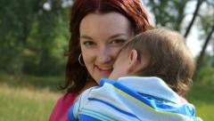 Loving mother with baby smiles at camera Stock Footage