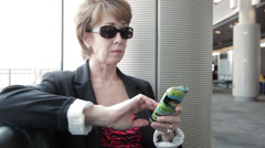 Businesswoman texting in a airport Stock Footage