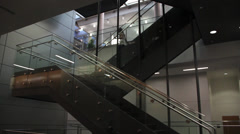 People walking down a modern stairway inside a building Stock Footage