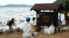 OIL SPILL DISASTER WORKERS CLEAN TROPICAL BEACH Stock Footage