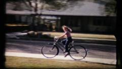 378 - girl rides her bike on the sidewalks in suburbia - vintage film home movie Stock Footage