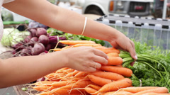 Female Hands Choosing Organice Carrots at Farmers Market Stock Footage