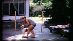 Dog training in the backyard by little girl, 375 vintage film home movie Stock Footage