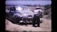 365 - men digging out car stuck in sand dune - vintage film home movie Stock Footage