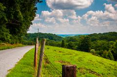 fence and rural backroad atop a hill in baltimore county, maryland. - stock photo