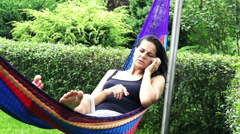 Woman with the cellphone receiving bad news in a hammock, slow motion shot at 60 Stock Footage