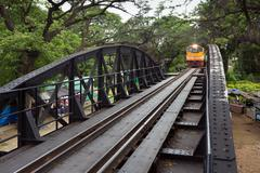 Train approaching on river kwai Stock Photos