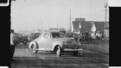 Cars going around corner. (Vintage 1940's 16mm film footage). Stock Footage