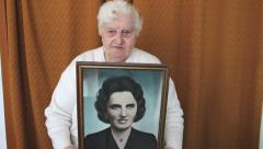 Old woman with her portrait when she was young. Ageing and evanescence. 3 Stock Footage
