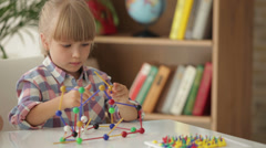 Cute little girl sitting at table playing with construction set and looking Stock Footage