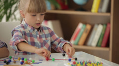 Cute little girl sitting at table playing with logic toy and smiling at camera - stock footage