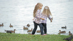 Two cute little girls at park feeding ducks Stock Footage
