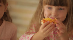 Two funny little girls eating pizza and smiling at camera Stock Footage