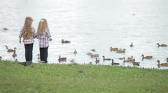 Two little girls feeding ducks at park - stock footage