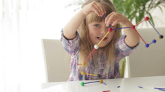 Two little girls sitting at desk playing with toys and smiling at camera - stock footage