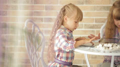 Two little girls sitting at table at cafe and using touchpads Stock Footage