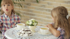 Two pretty little girls sitting at table at cafe and talking over cup of tea. - stock footage