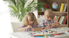 Two little girls sitting at table playing with logic toys and smiling at camera - stock footage