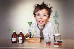 Crazy scientist. Young boy performing experiments Stock Photos