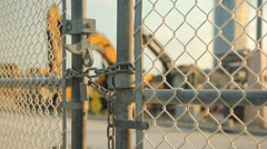 Locked gate at worksite. Heavy equipment. - stock footage