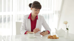 Attractive young woman sitting at table with cup of tea and using cellphone Stock Footage
